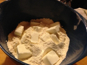 Sift together flour, baking powder, and salt.  Cut shortening in with a pastry cutter.  Mix in water and transfer to pie board, handling minimally.